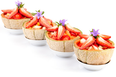 Fruit salad in half melons decorated with strawberries and mint, over white background. photo