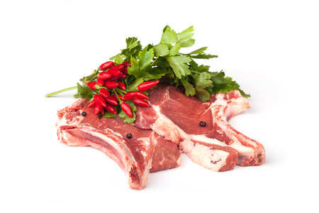 Raw t-bone steaks with chili peppers and parsley, over white background. photo