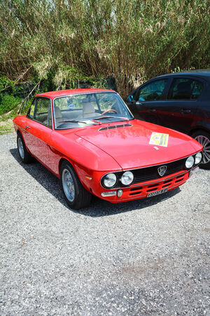 ANGUILLARA SABAZIA, LAZIO, ITALY - APRIL 6, 2014: Red vintage Lancia Fulvia participating at the 11-th meeting of spring memorial Luciano Polverari. Fulvias are notable for their role in automobile racing history, including winning the International Rally