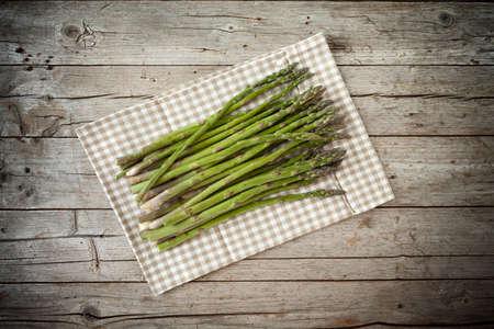 overhead shot: Bunch of fresh asparagus on wood background, overhead shot.