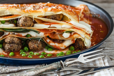 neapolitan: Closeup of lasagna made with meatballs, mozzarella cheese, parmesan, basil, green peas and tomato sauce. Is a traditional neapolitan lasagna except the green peas, not used in the base recipe.