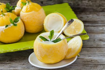 Desery letnie - Lemon lody wewnątrz świeżych cytryn ozdobione liśćmi mięty. Zdjęcie Seryjne