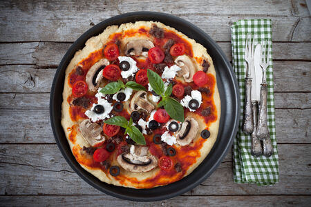 overhead shot: Overhead shot of pizza with mushrooms, minced sausage, tomatoes, olives, basil and cheese.