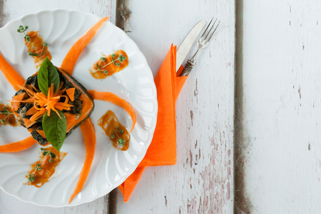 overhead shot: Overhead shot of plate with bicolor chard and pumpkin gnocchi timbale decorated with fresh pumpkin and basil leaves.
