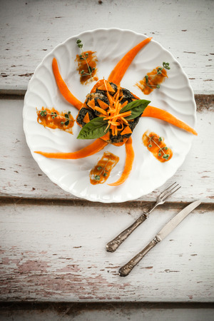 overhead shot: Overhead shot of plate with moulded bicolor gnocchi with pumpkin and chard cream, decorated with fresh pumpkin and basil leaves.