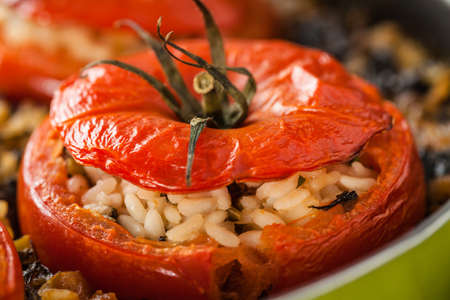 Closeup of baked tomato filled with rice and chard, typical recipe of Italian vegetarian cuisine. photo