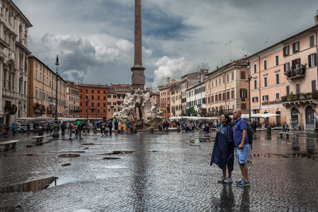 ROME, ITALY - JUNE 18, 2014:  Piazza Navona under the rain with many tourists not daunted  by the bad weather hitting Rome for the fourth consecutive day.