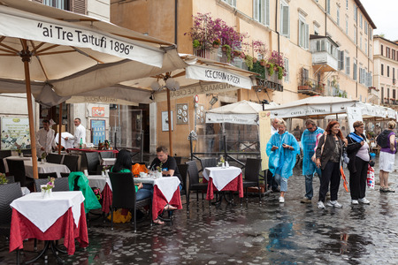 consecutive: ROME, ITALY - JUNE 18, 2014: Piazza Navona under the rain with many tourists not daunted  by the bad weather hitting Rome for the fourth consecutive day. Restaurant Ai Tre Tartufi. Editorial