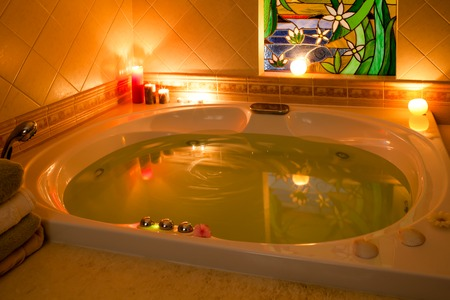 Nice atmosphere in bathroom with jacuzzi filled with water and bath salts, in the candle light.