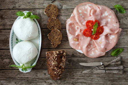 overhead shot: Fresh Italian appetizer:  with sliced mortadella, mozzarella and wholemeal bread with seeds. Overhead shot.