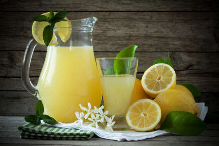 Jug and glass with lemon juice decorated with fresh lemons and mint leaves. photo
