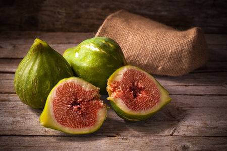 Old style still life with ripe fresh figs on wooden table. photo