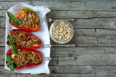overhead shot: Half bell peppers stuffed with tuna fish and pine seeds, overhead shot.