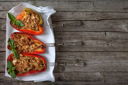 overhead shot: Half bell peppers stuffed with tuna fish and pine seeds, decorated with basil, overhead shot. Stock Photo