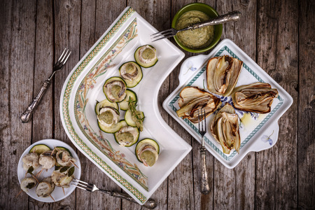 overhead shot: Overhead shot of plates with canapes of zucchini with fillet of red mullet and herbs pesto and grilled fennel.