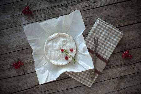 overhead shot: Overhead shot of Camembert cheese on piece of paper, decorated with redcurrants and thyme.