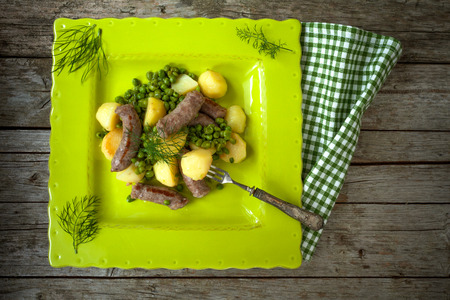 overhead shot: Overhead shot of plate with sausages, potatoes and green peas. Stock Photo