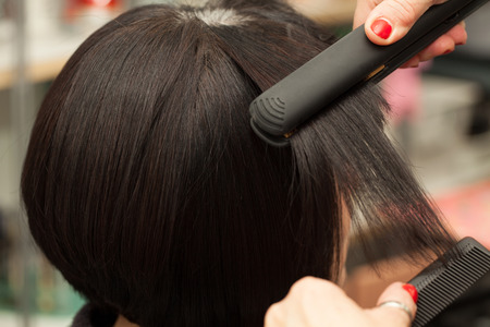 Hair straightening by a hairdresser in a professional salon, closeup shot.
