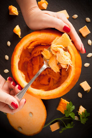 Woman hands holding spoon with pumpkin pulp during the operation of carving.