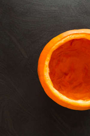 overhead shot: Food backgrounds - Overhead shot of half empty pumpkin on black background. Stock Photo