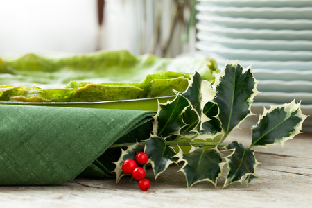 Detail of spinach lasagna pan on Christmas table decorated with holly, selective focus.