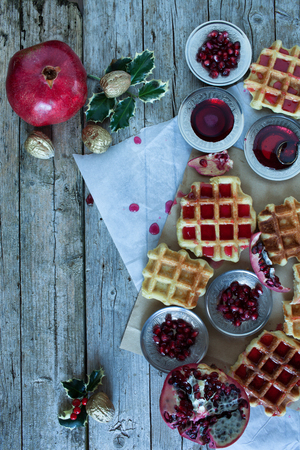 Christmas table with fresh baked waffle and pomegranate sorbet decorated with holly and pomegranate seeds. photo