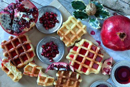 overhead shot: Golden fresh baked waffle topped with pomegranate sorbet, overhead shot.