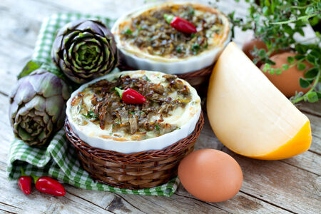 Table with vegetable flans made with artichokes, spinach, cheese and ground meat, decorated with chili peppers. photo
