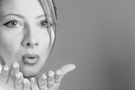 blow kiss: Portrait in black and white of sensual Caucasian woman blowing kisses. Stock Photo