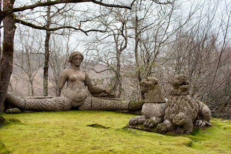 echidna: Mythical figures in the Sacred Wood of Bomarzo, Italy: Echidna at left with woman body and serpent tail and two lions at right.