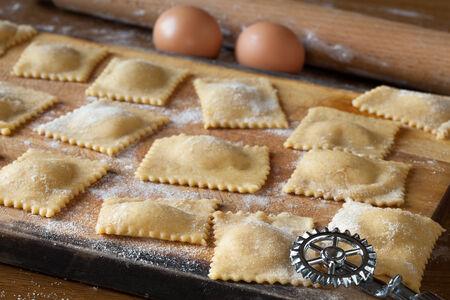Raw agnolotti pasta on cutting board.