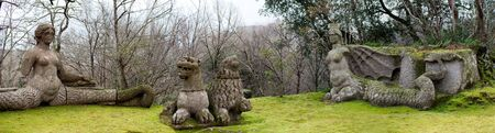 echidna: Two mythical figures in the Sacred Wood of Bomarzo, Italy: Echidna at left with woman body and serpent tail and Fury at the right side, a demon of the underworld in the popular primitive beliefs with two lions at center.