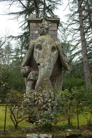 surmounted: An Elephant statue surmounted by a tower, which crushes with his proboscis a Legionnaire.  This is one of the largest sculptures in the Bomarzo gardens, Viterbo.