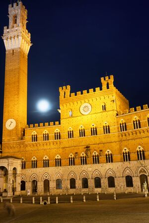 townhall: Siena Piazza del Campo with Public Palace and Mangia Tower in a night with full moon. Stock Photo