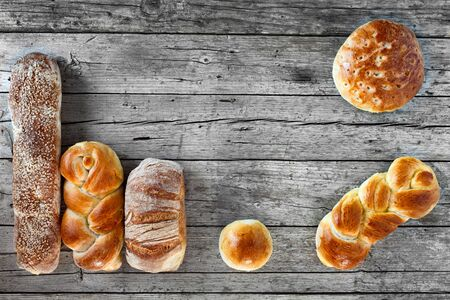 Various bread types, overhead shot on wood background. photo