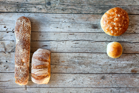 Various types of Italian bread, overhead shot, on wood background. photo