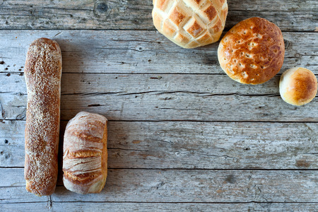 Various types of bread, overhead shot on wood background. photo