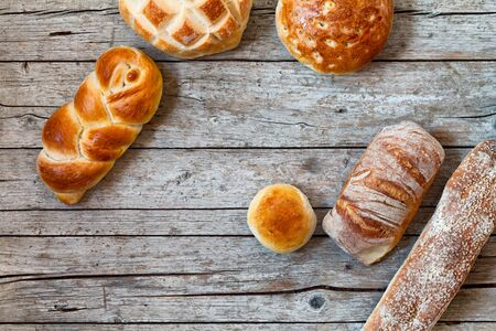 Overhead shot of various types of bread on wood background. photo