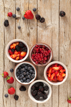Soft fruits in bowls photographed from above: strawberries, blackberries, blueberries and redcurrants.