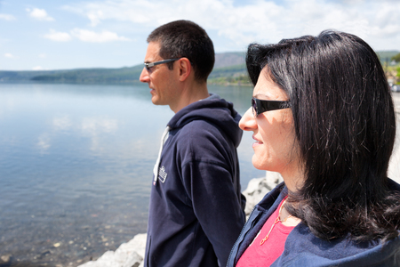 profile view: Profile view of middle-aged caucasian couple watching the lake in a sunny spring day.