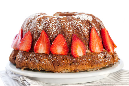 icing sugar: Bundt cake with strawberries, sprinkled with icing sugar. Stock Photo