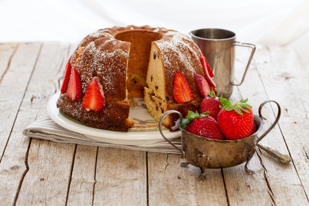 icing sugar: Rustic style bundt cake decorated with strawberries and sprinkled with icing sugar.