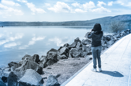 cinematic: Woman taking pictures of the lake, cinematic effect applied.