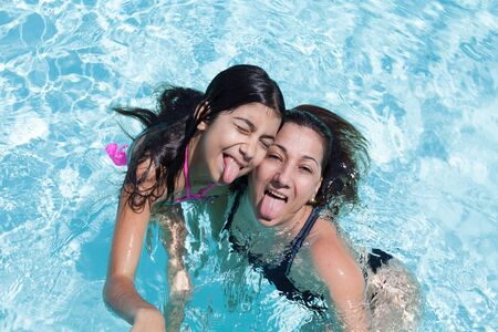 tongues: Happy mother and daughter sticking their tongues out having fun in the swimming pool.