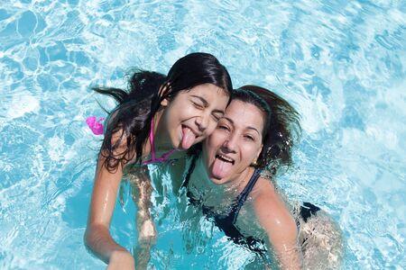 sacar la lengua: Madre e hija felices sacando la lengua que se divierten en la piscina.