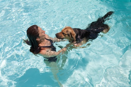 Woman swimming with her dog in the swimming pool.