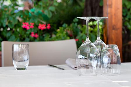 vasos de agua: Vino y vasos de agua volvieron al revés, en la mesa al aire libre. Foto de archivo