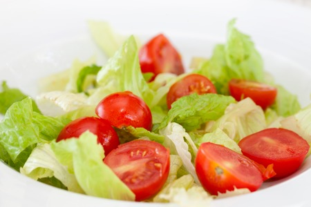 Closeup of salad with cherry tomatoes and lettuce, low calorie plate.
