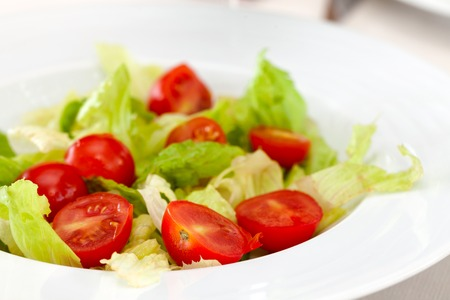Close-up of plate with lettuce and cherry tomatoes in salad.