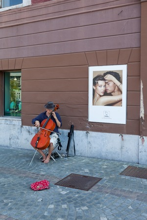 busker: LJUBLJANA, SLOVENIA - AUGUST 31, 2015: Street busker playing the contrabass in the old center of the city. Editorial